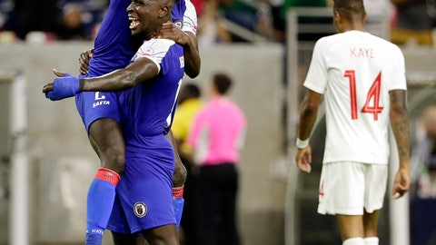 <p>               Haiti defender Carlens Arcus is held up by defender Andrew Jean Baptiste as Canada defender Mark-Anthony Kaye (14) walks off the field after Haiti defeated Canada 3-2 in a CONCACAF Gold Cup soccer quarterfinal Saturday, June 29, 2019, in Houston. (AP Photo/Michael Wyke)             </p>