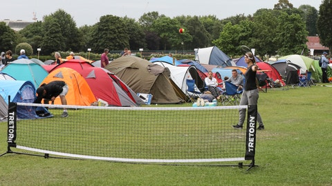 """<p>               In this Tuesday, July 9, 2019, some tennis fans play a game as they wait in line for tickets to enter the Wimbledon Tennis Championships in London. For many the Wimbledon experience starts in a tent as they gather in a small park across from the tournament grounds to camp out, some for days, in the hope of getting a ticket to Centre Court as they are released each day. """"The Queue"""" is a decades-old tradition that has grown to become its own phenomenon.(AP Photo/Natasha Livingstone)             </p>"""