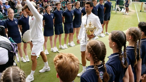 <p>               Serbia's Novak Djokovic, right, and Switzerland's Roger Federer leave the court holding their trophies after the men's singles final match of the Wimbledon Tennis Championships in London, Sunday, July 14, 2019. (AP Photo/Tim Ireland)             </p>