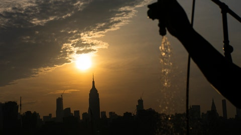 <p>               The sun rises over New York City and the Empire State Building while a man sprays water at Pier A on Saturday, July 20, 2019 in Hoboken, N.J. Temperatures in the high 90s are forecast for Saturday and Sunday with a heat index well over 100. Much of the nation is also dealing with high heat.   (AP Photo/Eduardo Munoz Alvarez)             </p>