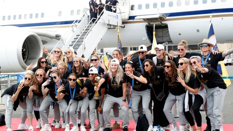 <p>               Members of the United States women's soccer team, winners of a fourth Women's World Cup, pose with the trophy by their plane after arriving at Newark Liberty International Airport, Monday, July 8, 2019, in Newark, N.J. Julie Ertz holds the trophy, Megan Rapinoe, front right, gestures, and Alex Morgan, back left, also gestures. (AP Photo/Kathy Willens)             </p>