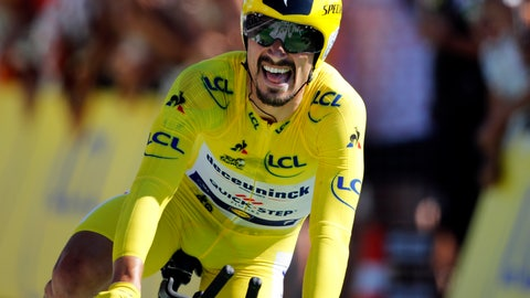 <p>               France's Julian Alaphilippe wearing the overall leader's yellow jersey crosses the finish line to win the thirteenth stage of the Tour de France cycling race, an individual time trial over 27.2 kilometers (16.9 miles) with start and finish in Pau, France, Friday, July 19, 2019. (AP Photo/Christophe Ena)             </p>