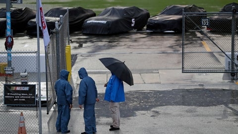 <p>               Races cars sit covered and idle on pit road as track workers gather nearby during a rain storm delaying a NASCAR Xfinity Series auto race at Daytona International Speedway, Friday, July 5, 2019, in Daytona Beach, Fla. (AP Photo/John Raoux)             </p>