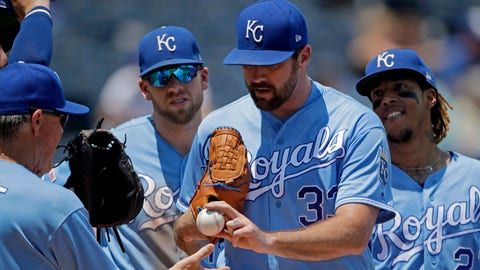 Kansas City Royals starting pitcher Brian Flynn, second from right, hands the ball to manager Ned Yost, left, as he comes out of a baseball game during the third inning against the Detroit Tiger, Sunday, July 14, 2019, in Kansas City, Mo. (AP Photo/Charlie Riedel)