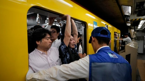 <p>               In this July 30, 2019, photo, a station attendant watches as a commuter struggles to squeeze himself into an overcrowded train during morning rush hours at Akasaka Mitsuke Station in Tokyo. Tokyo has one of the most advanced public transport systems in the world, but with less than one year to go before the city hosts the 2020 Olympic Games, local governments, companies and commuters are bracing for unprecedented strain the events could put on rail transit and highways. (AP Photo/Jae C. Hong)             </p>