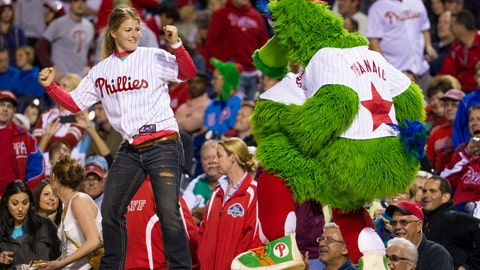 """<p>               File-This Sept. 16, 2013. file photo shows the Phillies Phanatic dancing with a fan on the dugout during the eighth inning of a baseball game in Philadelphia. The Philadelphia Phillies have sued the New York company that created the Phanatic mascot to prevent the green fuzzy fan favorite from becoming a free agent. In a complaint filed Friday, Aug. 2, 2019, in U.S. District Court in Manhattan, the team alleged Harrison/Erickson threatened to terminate the Phillies' rights to the Phanatic next year and """"make the Phanatic a free agent"""" unless the team renegotiated its 1984 agreement to acquire the mascot's rights. (AP Photo/Chris Szagola, File)             </p>"""