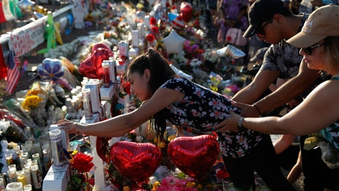 <p>               A woman leans over to write a message on a cross at a makeshift memorial at the scene of a mass shooting at a shopping complex, Tuesday, Aug. 6, 2019, in El Paso, Texas. (AP Photo/John Locher)             </p>