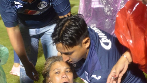 <p>               A soccer fan affected by tear gas fired by police is helped on the field by fellow fans after a deadly fight broke out before the start of a game between Motagua and Olimpia, inside the national stadium in Tegucigalpa, Honduras, late Saturday, Aug. 17, 2019. The fight between fans of rival soccer teams outside the stadium left three people dead and led to the suspension of the game. (Victor Colindres/La Tribunal via AP)             </p>