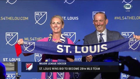 Ownership group leader Carolyn Kindle Betz and league commissioner Don Garber display a banner signifying St. Louis as the newest MLS franchise.