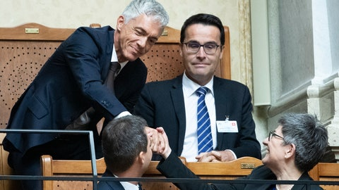 <p>               Re-elected Swiss Federal Prosecutor Michael Lauber, on the left, receives congratulations from Nicoletta della Valle, Director Fedpol, right, during the autumn session of the Swiss Federal Council in Bern, Switzerland, Wednesday, Sept. 25, 2019. Switzerland's lawmakers have given attorney general Michael Lauber four more years in office, he was renewed for a third mandate. (Peter Schneider/Keystone via AP)             </p>