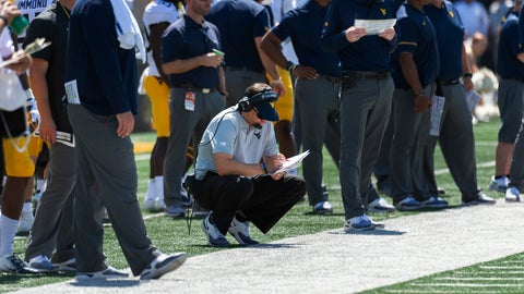 <p>               West Virginia head coach Neal Brown looks over his play book as he squats on the sideline during the second half of an NCAA college football game against Missouri Saturday, Sept. 7, 2019, in Columbia, Mo. Missouri won the game 38-7. (AP Photo/L.G. Patterson)             </p>