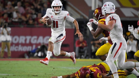 <p>               Fresno State quarterback Jorge Reyna, left, escapes a tackle by Southern California defensive lineman Jay Tufele, below, as defensive lineman Christian Rector, second from right, gives chase and tight end Jared Rice runs in during the first half of an NCAA college football game Saturday, Aug. 31, 2019, in Los Angeles. (AP Photo/Mark J. Terrill)             </p>