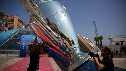 <p>               Workers install a giant replica of the Champions League trophy ahead of the UEFA group stage draw outside the Grimaldi Forum, in Monaco, Thursday, Aug. 29, 2019. (AP Photo/Daniel Cole)             </p>