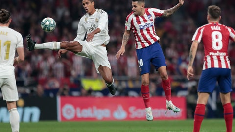<p>               Real Madrid's Raphael Varane jumps to kick the ball before Real Madrid's Marco Asensio, center right, during the Spanish La Liga soccer match between Atletico Madrid and Real Madrid at the Wanda Metropolitano stadium in Madrid, Saturday, Sept. 28, 2019. (AP Photo/Bernat Armangue)             </p>