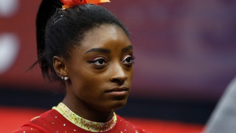 <p>               FILE - In this July 28, 2018, file photo, Olympic champion Simone Biles talks with her coach before the start of the U.S. Classic gymnastics competition in Columbus, Ohio. Biles says she's struggling with the arrest of her brother who was charged in a shooting that left three dead. She said in a tweet Monday, Sept. 2, 2019, that her heart aches for everyone involved, especially the victims and their families. (AP Photo/Jay LaPrete, File)             </p>