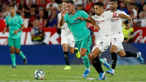 <p>               Real Madrid's Eden Hazard, center, is challenged by Sevilla's Daniel Carrico during the Spanish La Liga soccer match between Sevilla and Real Madrid at the Ramon Sanchez Pizjuan stadium in Seville, Spain, Sunday, Sept. 22, 2019. (AP Photo/Miguel Morenatti)             </p>