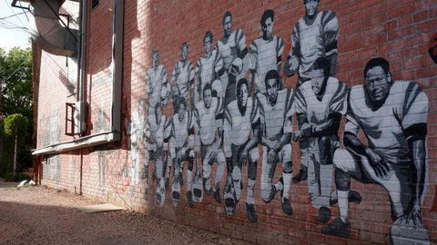 <p>               In this Wednesday, Sept. 11, 2019 photo shows part of an alleyway mural in downtown Laramie, Wyo., that honors the Black 14. The Black 14 were black athletes dismissed from the University of Wyoming football team in 1969 for seeking to protest racism by wearing black armbands in a game against Brigham Young University. The university plans to dedicate a plaque honoring the group at War Memorial Stadium on Friday. (AP Photo/Mead Gruver)             </p>