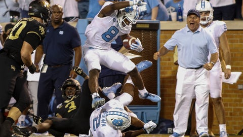 <p>               North Carolina running back Michael Carter (8) leaps over Wake Forest defensive back Nasir Greer (3) and North Carolina wide receiver Dyami Brown (2) during the second half of an NCAA college football game in Winston-Salem, N.C., Friday, Sept. 13, 2019. Wake Forest won 24-18. (AP Photo/Nell Redmond)             </p>
