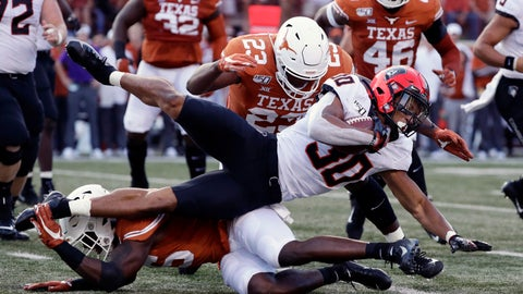 <p>               Oklahoma State running back Chuba Hubbard (30) is stopped by Texas defensive lineman Peter Mpagi, bottom, and linebacker Jeffrey McCulloch (23) during the first half of an NCAA college football game Saturday, Sept. 21, 2019, in Austin, Texas. (AP Photo/Eric Gay)             </p>