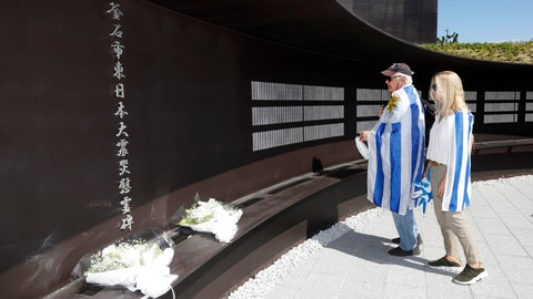 <p>               A couple from Uruguay wrapping themselves with their national flags visits Kamaishi Memorial Park, a facility to pay tribute to victims of the 2011 earthquake and tsunami, before the Rugby World Cup Pool D game between Fiji and Uruguay, in Kamaishi, northeastern Japan, Wednesday, Sept. 25, 2019. The both teams will honor the first World Cup game at Kamaishi Recovery Memorial Stadium in the small fishing town where more than 1,000 were killed by the disaster. (Yusuke Ogata/Kyodo News via AP)             </p>