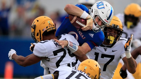 Kansas quarterback Carter Stanley (9) is tackled by West Virginia safety Sean Mahone (29) and linebacker Exree Loe (17) during the first half of an NCAA college football game in Lawrence, Kan., Saturday, Sept. 21, 2019. (AP Photo/Orlin Wagner)