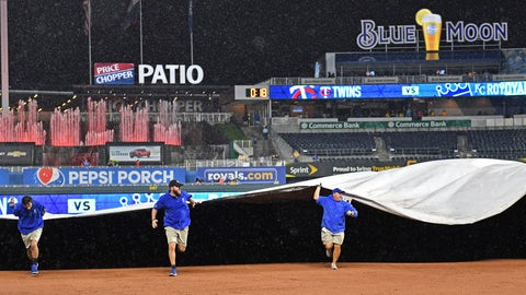 Sep 27, 2019; Kansas City, MO, USA; The grounds crew pulls out the tarp during a rain delay in the seventh inning of a game between the Kansas City Royals and Minnesota Twins at Kauffman Stadium. Mandatory Credit: Peter G. Aiken-USA TODAY Sports
