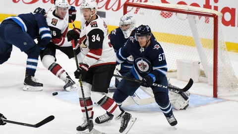 <p>               Winnipeg Jets' Gabriel Bourque (57) and Arizona Coyotes' Carl Soderberg (34) watch as the puck is shot toward Jets goalie Connor Hellebuyck during the first period of an NHL hockey game Tuesday, Oct. 15, 2019, in Winnipeg, Manitoba. (Fred Greenslade/The Canadian Press via AP)             </p>