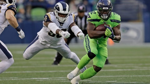 <p>               Seattle Seahawks running back Chris Carson, right, carries as Los Angeles Rams outside linebacker Samson Ebukam, left, leaps to attempt a tackle during the first half of an NFL football game Thursday, Oct. 3, 2019, in Seattle. (AP Photo/Stephen Brashear)             </p>