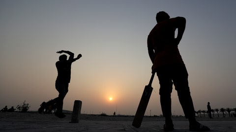 <p>               A man comes in to bowl during a cricket match on a patch of wasteland in Doha, Qatar, Friday, Oct. 4, 2019. At dozens of makeshift pitches on wasteland around Doha, workers from all over South Asia gather to play on their one free day of the week. The stadium hosting the world track and field championship, and the arenas for the 2022 soccer World Cup, are at best distant lights on the horizon. (AP Photo/Petr David Josek)             </p>