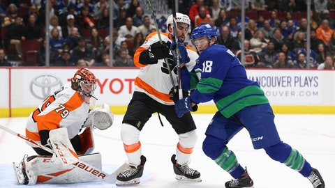 <p>               Vancouver Canucks' Jake Virtanen (18) fights for the puck with Philadelphia Flyers' Matt Niskanen (15) as Flyers goalie Carter Hart (79) watches during the first period of an NHL hockey game Saturday, Oct. 12, 2019, in Vancouver, British Columbia. (Ben Nelms/The Canadian Press via AP)             </p>
