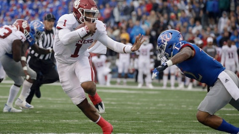 <p>               Oklahoma quarterback Jalen Hurts (1) gets past Kansas safety Jeremiah McCullough (12) as he runs the ball during the first half of an NCAA college football game Saturday, Oct. 5, 2019, in Lawrence, Kan. (AP Photo/Charlie Riedel)             </p>
