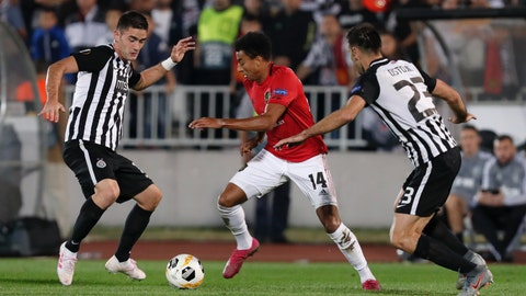 <p>               Manchester United's Jesse Lindgard, center, challenges for the ball with Partizan's Bojan Ostojic during the Europa League group L soccer match between Partizan Belgrade and Manchester United at the Partizan stadium in Belgrade, Serbia, Thursday, Oct. 24, 2019. (AP Photo/Darko Vojinovic)             </p>