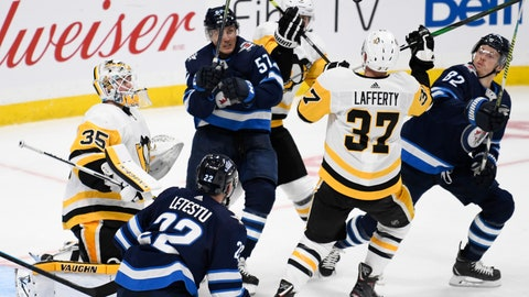 <p>               Pittsburgh Penguins goaltender Tristan Jarry (35), Sam Lafferty (37) and Winnipeg Jets' Gabriel Bourque (57) and Mason Appleton (82) follow the bouncing puck during the third period of an NHL hockey game, Sunday, Oct. 13, 2019, in Winnipeg, Manitoba. (Fred Greenslade/The Canadian Press via AP)             </p>