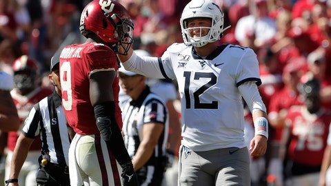 <p>               West Virginia quarterback Austin Kendall (12) jokes around with Oklahoma linebacker Kenneth Murray (9) between plays in the second half of an NCAA college football game in Norman, Okla., Saturday, Oct. 19, 2019. Oklahoma won 52-14. (AP Photo/Alonzo Adams)             </p>