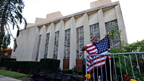 <p>               A man places an American flag outside the Tree of Life synagogue in Pittsburgh on Sunday, Oct. 27, 2019, the first anniversary of the shooting at the synagogue that killed 11 worshippers. (AP Photo/Gene J. Puskar)             </p>