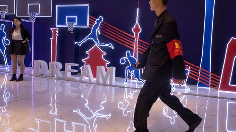 """<p>               In this Friday, Oct. 11, 2019, photo, a security guard walks past neon light decor depicting basketball players and silhouette of iconic Chinese buildings in Beijing. When Houston Rockets' general manager Daryl Morey tweeted last week in support of anti-government protests in Hong Kong, everything changed for NBA fans in China. A new chant flooded Chinese sports forums: """"I can live without basketball, but I can't live without my motherland.""""(AP Photo/Ng Han Guan)             </p>"""