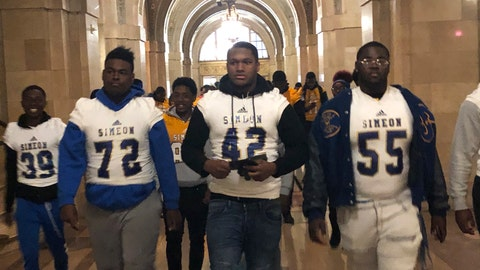 <p>               George Robinson (72) and Ronald Haggins (42) with members of the Simeon High School football team appear at City Hall Friday, Oct. 25, 2019, shows in Chicago. A strike by school teachers in Chicago has spread from the picket line to the playing field. Thousands of high school athletes, shut out of class for ten days, are arguing, rallying and even filing lawsuits for the chance to compete in postseason play. Hanging in the balance, they say, are not just the pursuit of championship glory, but scholarships, perhaps an otherwise-lost opportunity to attend college and, in some cases, to escape drugs and violence in city neighborhoods.(AP Photo/Don Babwin)             </p>