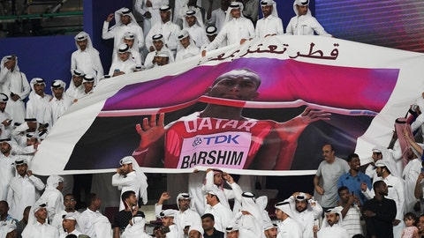 <p>               Spectators hold up a poster of high jumper Mutaz Essa Barshim, of Qatar, at the World Athletics Championships in Doha, Qatar, Friday, Oct. 4, 2019. (AP Photo/David J. Phillip)             </p>