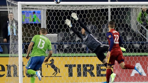 <p>               Real Salt Lake goalkeeper Nick Rimando, center, leaps as a shot goes wide and Seattle Sounders forward Jordan Morris, left, and Real Salt Lake defender Aaron Herrera, right, watch during the first half of an MLS Western Conference semifinal playoff soccer match Wednesday, Oct. 23, 2019, in Seattle. (AP Photo/Ted S. Warren)             </p>
