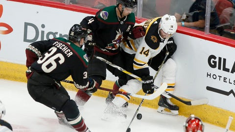 <p>               Boston Bruins' Chris Wagner (14) gets pinned up against the boards by the Arizona Coyotes' Niklas Hjalmarsson (4) and Christian Fischer (36) during the second period of an NHL hockey game Saturday, Oct. 5, 2019, in Glendale, Ariz. (AP Photo/Darryl Webb)             </p>