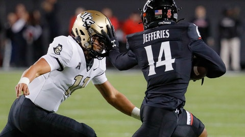 <p>               Cincinnati cornerback Cam Jefferies (14) stiff-arms UCF quarterback Dillon Gabriel (11) after intercepting a pass during the first half of an NCAA college football game Friday, Oct. 4, 2019, in Cincinnati. (AP Photo/John Minchillo)             </p>