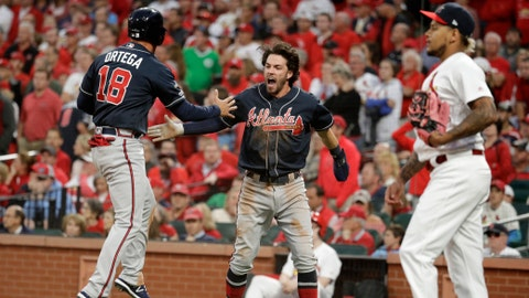 Atlanta Braves' Dansby Swanson, center, and Rafael Ortega, left, celebrate in front of St. Louis Cardinals relief pitcher Carlos Martinez after scoring during the ninth inning in Game 3 of a National League Division Series on Sunday, Oct. 6, 2019, in St. Louis. (AP Photo/Charlie Riedel)
