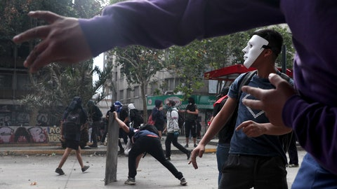 <p>               A mask demonstrator clash with the police during an anti-government protest in Santiago, Tuesday, Nov. 5, 2019. Chileans have been taking to the streets and clashing with the police to demand better social services and an end to economic inequality, even as the government announced that weeks of demonstrations are hurting the country's economic growth. (AP Photo/Esteban Felix)             </p>