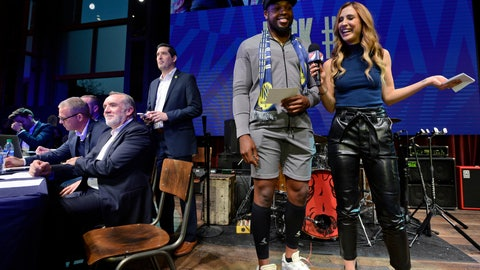 <p>               Tennessee Titans running back Derrick Henry laughs with MLS host Susannah Collins before announcing the team's second selection during the Major League Soccer expansion draft Tuesday, Nov. 19, 2019, in Nashville, Tenn. Nashville SC selected Zarek Valentin from the Portland Timbers. (AP Photo/Mark Zaleski)             </p>