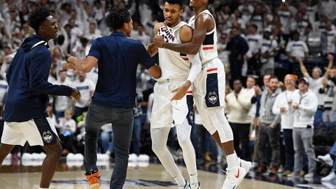 <p>               Connecticut's Tyler Polley, second from right, is congratulated by teammates Christian Vital, right, Temi Aiyegbusi, left, and James Bouknight during the second half of an NCAA college basketball game against Florida, Sunday, Nov. 17, 2019, in Storrs, Conn. (AP Photo/Jessica Hill)             </p>