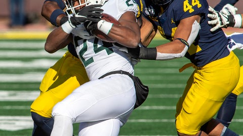 <p>               Michigan State running back Elijah Collins (24) gets tackled by Michigan defensive back Josh Metellus, top left, and linebacker Cameron McGrone (44) in the first quarter of an NCAA college football game in Ann Arbor, Mich., Saturday, Nov. 16, 2019. Michigan won 44-10. (AP Photo/Tony Ding)             </p>