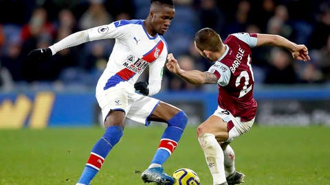 <p>               Crystal Palace's Wilfried Zaha, left, and Burnley's Phil Bardsley battle for the ball during the English Premier League soccer match at Turf Moor, Burnley, England, Saturday Nov. 30, 2019. (Martin Rickett/PA via AP)             </p>
