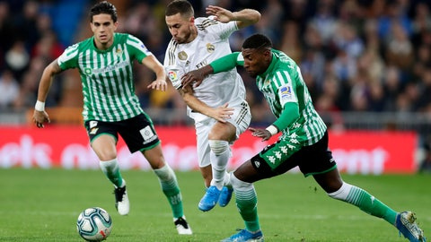 <p>               Real Madrid's Eden Hazard, center, tries to get past Betis' Emerson, right, and Marc Bartra, left, during a Spanish La Liga soccer match between Real Madrid and Betis at the Santiago Bernabeu stadium in Madrid, Saturday, Nov. 2, 2019. (AP Photo/Manu Fernandez)             </p>