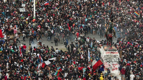 <p>               Police and demonstrators clash during an anti-government protest in Santiago, Chile, Monday, Nov. 4, 2019. Thousands of Chileans took to the streets again Monday to demand better social services, some clashing with police, as protesters demanded an end to economic inequality even as the government announced that weeks of demonstrations are hurting the country's economic growth. (AP Photo/Esteban Felix)             </p>