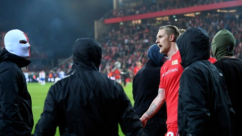 <p>               In this photo taken on Saturday, Nov. 2, 2019, Union's goal scorer Sebastian Polter tries to appease hooded fans after the team's final whistle and victory in the derby, in Berlin. Union Berlin is toasting goalkeeper Rafal Gikiewicz for his bravery in stopping his own masked fans from reaching Hertha Berlin supporters after the sides' fiery Berlin derby on Saturday. Gikiewicz angrily pushed one masked pitch invader back and urged others to return to their block. (Britta Pedersen/dpa via AP)             </p>